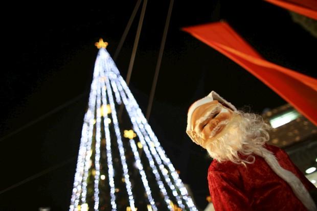 Um rapaz mascarado de Pai Natal junto à árvore da cidade de Nazaré, Israel