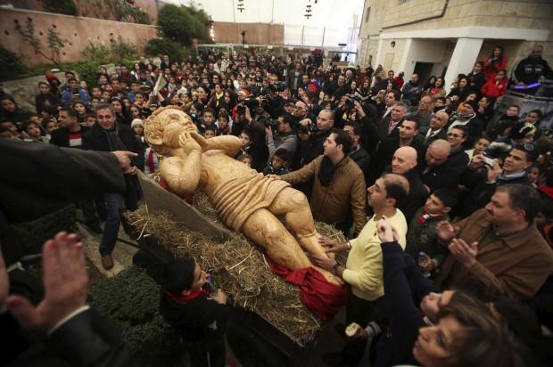 Menino de Jesus (de madeira) em palhas deitado: uma procissão palestiniana em Belém, Cisjordânia