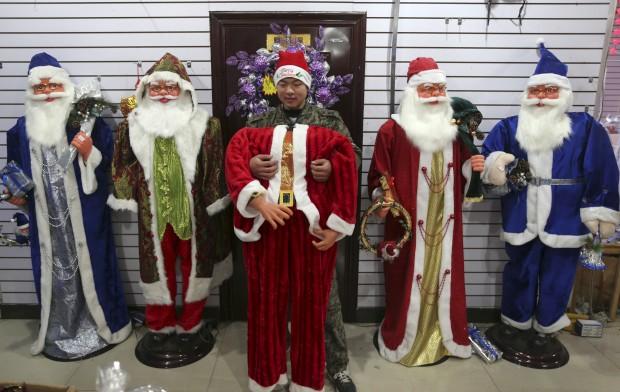 Na China, um vendedor arranja fatos do Pai Natal num mercado de Wuhan