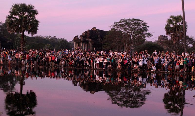 Aos primeiros raios de sol, os turistas aguardam para fotografarem um dos mais famosos templos do mundo, Angkor Wat, no Camboja. É o momento perfeito para admirar o monumento.