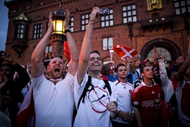 Os sempre bem dispostos adeptos dinamarqueses em dia de futebol no centro de Copenhaga