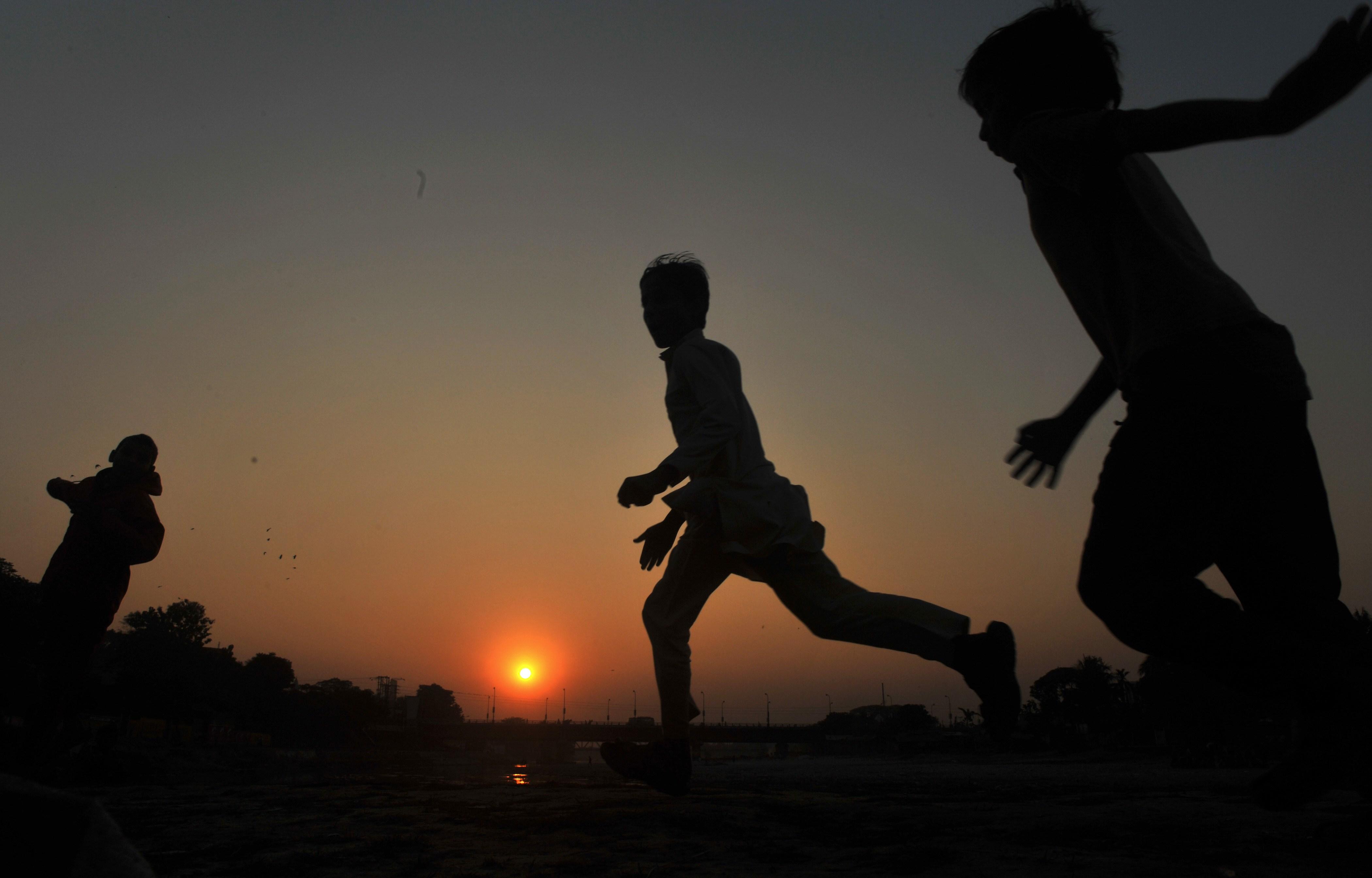 Crianças brincam durante o último pôr do sol de 2012. Siliguri, Índia