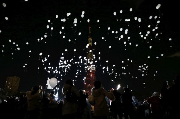 JAPÃO, 31.12.2012. Espectadores libertam balões perto da Torre de Tóquio, iluminada para celebrar a passagem de ano