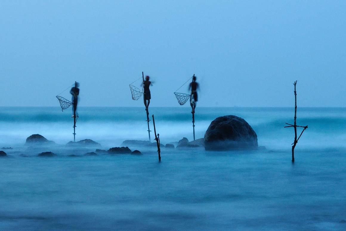 Menção Honrosa: Pescadores equilibram-se sobre galhos espetados nos corais, numa técnica que existe apenas no Sri Lanka. A longa exposição da foto mostra a instabilidade do conjunto.