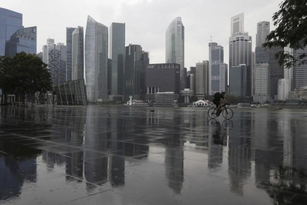 SINGAPURA, 3.1.2013. Um ciclista por entre o real e o reflexo no centro de negócios de Singapura