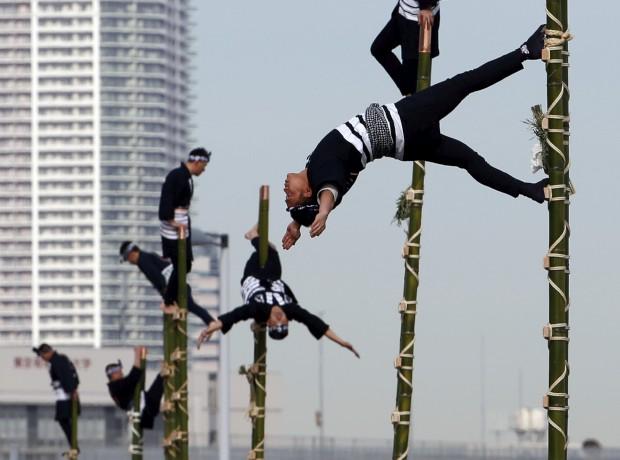 JAPÃO, 6.1.2013.  Membros da associação Edo para a prevenção de fogos exibem os seus dotes de ginastas numa demonstração de ano novo dos bombeiros de Tóquio