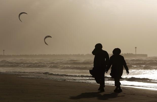 ISRAEL, 7.1.2013. Duas mulheres da comunidade de judeus ultra-ortodoxos caminham à beira-mar durante um dia de tempestade em Ashdod