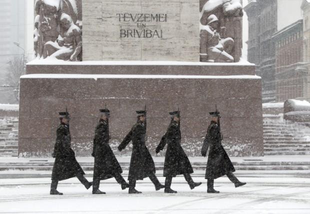 LETÓNIA, 10.1.2013. Guarda de honra marcha perto do Monumento à Liberdade durante uma tempestade de neve em Riga