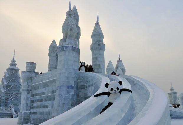 CHINA, 11.1.2013. Um empregado vestido de panda no festival de esculturas de neve e gelo em Harbin