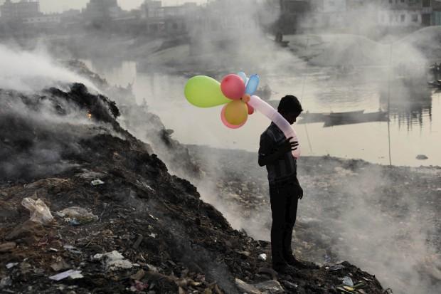 BANGLADESH, 19.01.2013. Um rapaz brinca com balões junto ao rio Buriganga (o fumo que se vê é de uma lixeira). Em Dhaka.