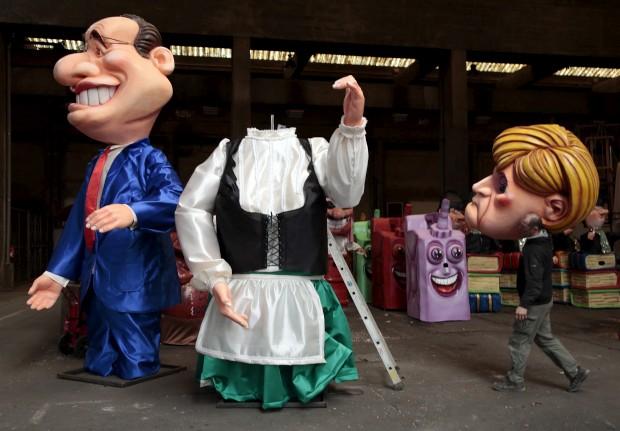FRANÇA, 12.02.2013. No Carnaval de Nice. Um trabalhador carrega a cabeça de uma figura gigante que representa Angela Merkel para ao pé da figura do primeiro-ministro francês, Hollande.