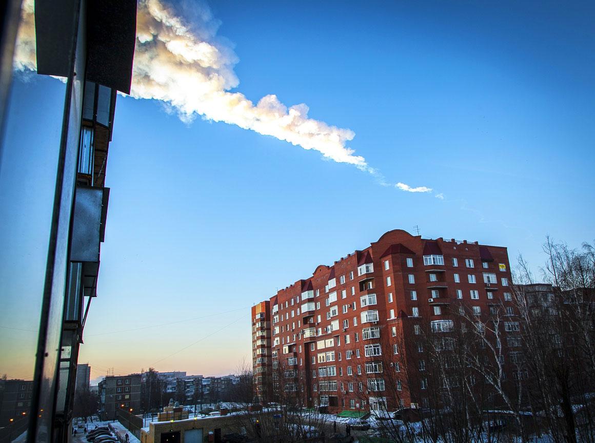 O rasto do meteoro por cima de um bloco de apartamentos em Cheliabinsk