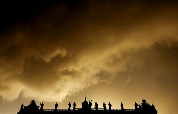 As silhuetas das estátuas no topo da Basílica sob nuvens de tempestade