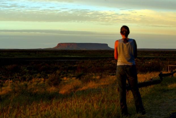 Na estrada para o célebre rochedo Uluru, o maior monólito do mundo e atracção turística por si só. Também antes conhecido como Ayers Rock ou, simplesmente, The Rock (A Rocha). A 310km de Alice Springs