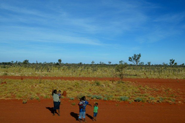 No deserto a norte de Alice Springs, um grupo de aborígenes acena para o comboio