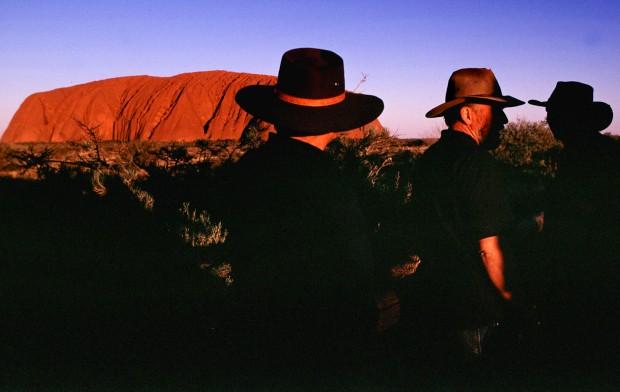 Um grupo de turistas observa o pôr-do-sol no Uluru
