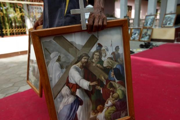 Um homem carrega um quadro com Jesus Cristo em Larantuca