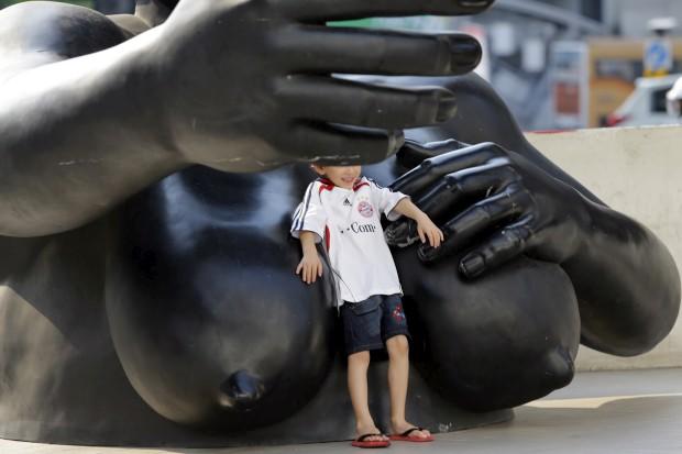 TAILÂNDIA; 27.02.2013. Um rapaz posa para a foto em frente a uma estátua no Centro de Arte e Cultura de Banguecoque