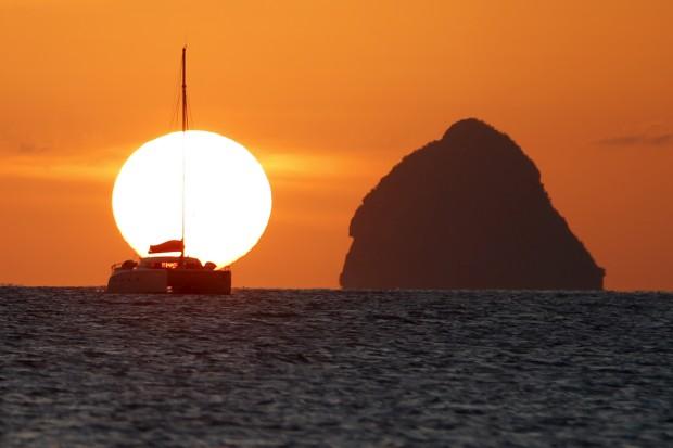 MARTINICA, 13.03.2013. O postal perfeito: foto captada ao pôr-do-sol na Martinica com um barco à vela perto de um icónico Rochedo do Diamante (Rocher du diamand)