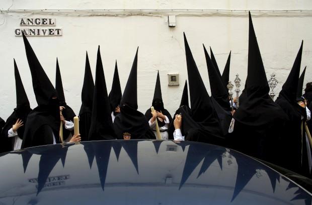 ESPANHA, 25.03.2013. Penitentes aguardam para participar na procissão de Santa Genoveva durante a Semana Santa em Sevilha