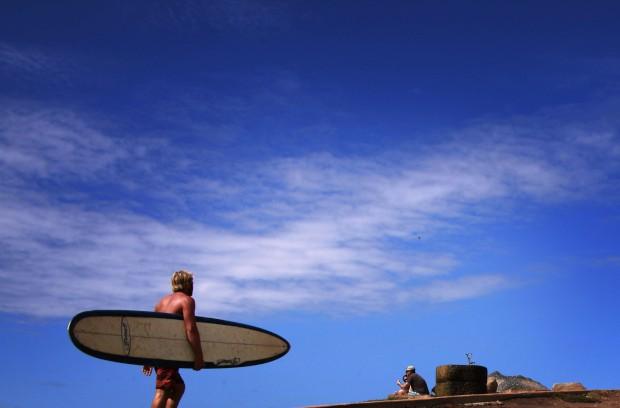 AUSTRÁLIA, 2.4.2013. Um surfista caminha pela Long Reef Beach num dia quente de Sydney