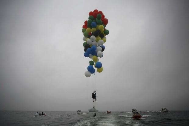 ÁFRICA DO SUL, 6.04.2013. Matt Silver-Vallance flutua sobre o mar utilizando balões com gás hélio. Voo do aeródromo de Robben Island pelo Atlântico, na Cidade do Cabo: 7km cumpridos para angariar fundos para o hospital pediátrico Nelson Mandela.