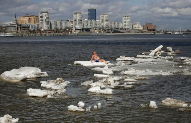 RÚSSIA, 26.04.2013. Nada como um banho de sol no gelo da Sibéria. Se duvida, pergunte ao sr. Vladimir Samsonov, da cidade de Zheleznogorsk, membro de um clube de natação de Inverno. No rio Yenisei