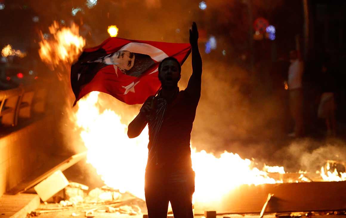 Os protestos chegaram entretanto a outras cidades. Em Ancara, um manifestante segura uma bandeira de of Mustafa Kemal Ataturk, fundador da Turquia moderna