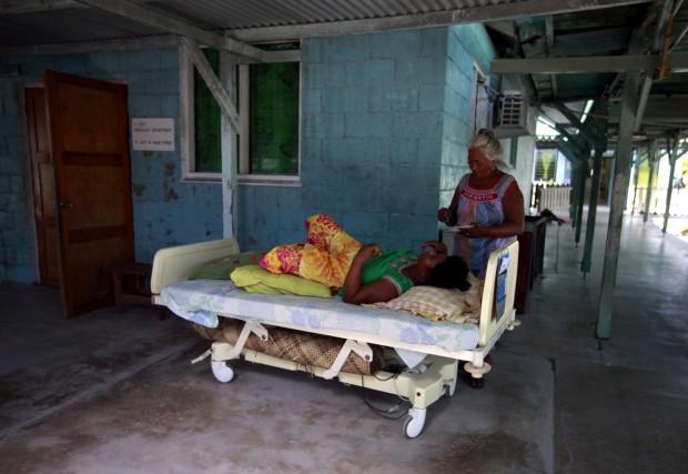 Uma mulher prepara-se para alimentar uma paciente de um hospital