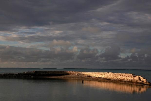 A nadar perto de uma parede construída para conter as marés cheias, perto de Eita