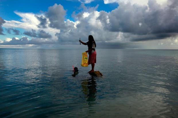 Binata Pinata, habitante da  ilhota de Bikeman, no topo de uma rocha, agarrando um peixe que o marido acabou de pescar