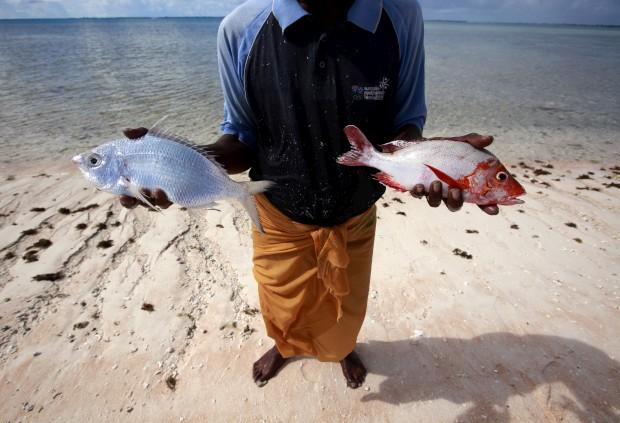 Kaibakia Pinata, habitante da ilhota de Bikeman, com o peixe que acabou de pescar