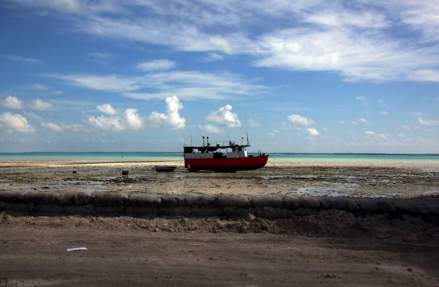 Um barco nas lamas do recife perto de uma lagoa na Tarawa do Sul
