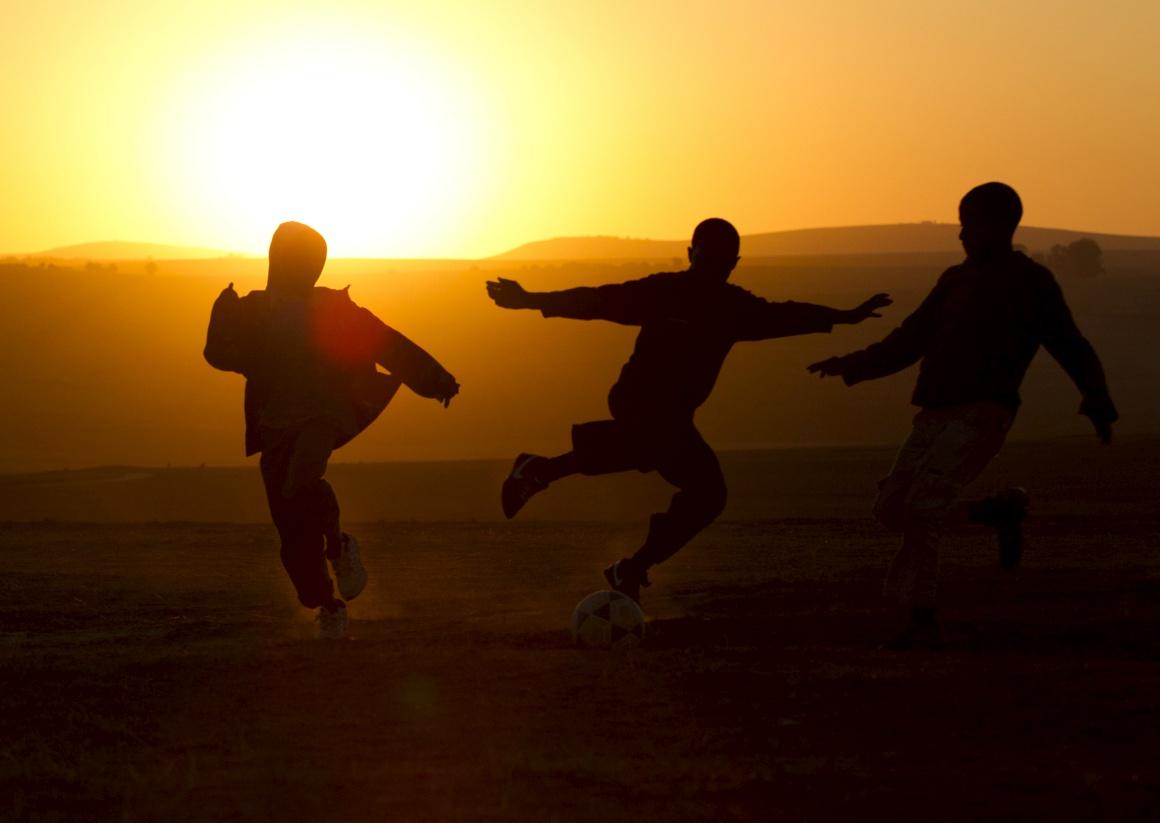ÁFRICA DO SUL, 28.6.2013. Rapazes jogam à bola ao entardecer perto da casa de Nelson Mandela