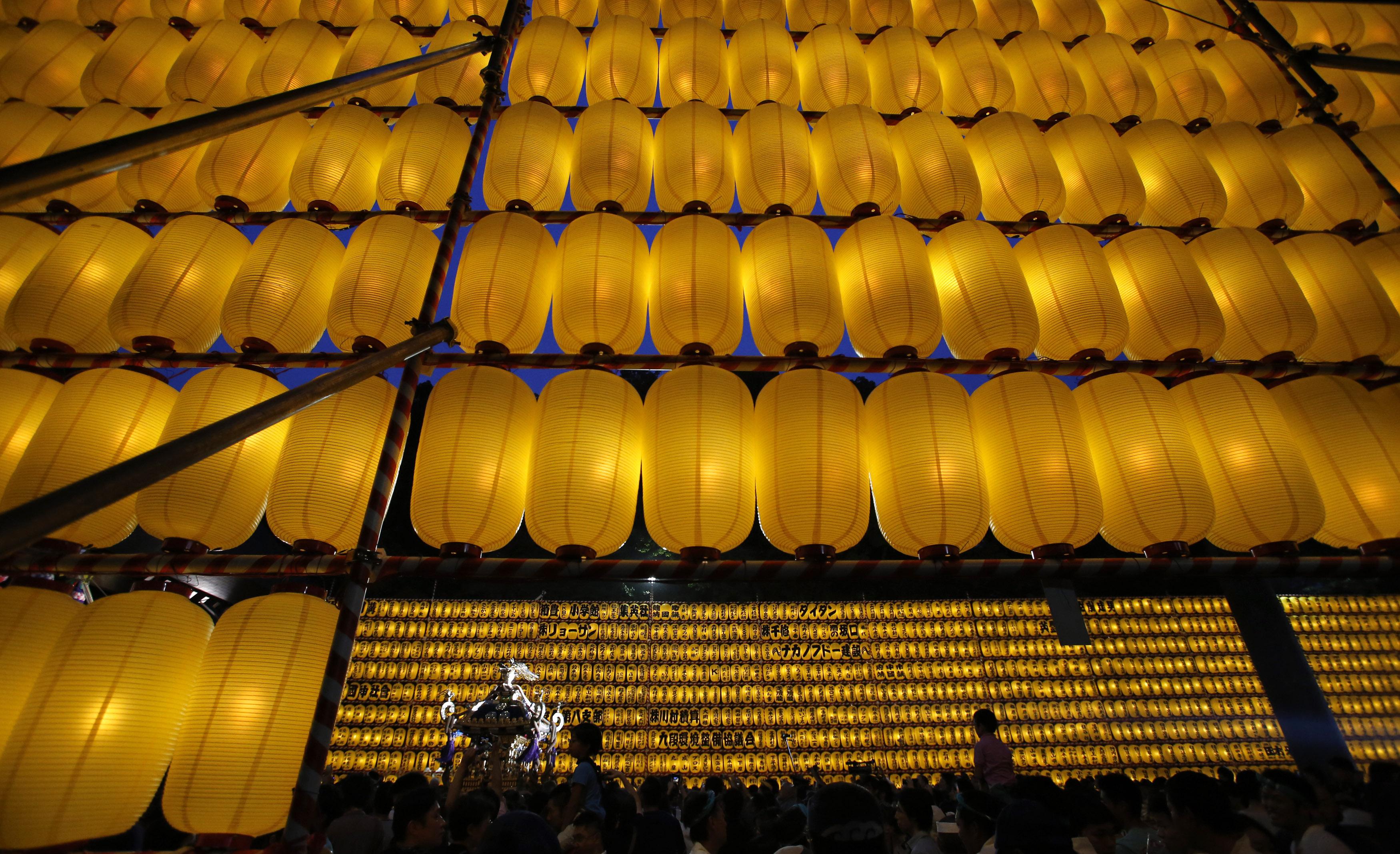JAPÃO, 13.7.2013. Uma procissão com um templo portátil por entre lanternas de papel durante o festival Mitama no Templo Yasukuni em Tóquio. Mais de 30 mil lanternas iluminam o recinto. Homenageiam-se os espíritos dos antepassados