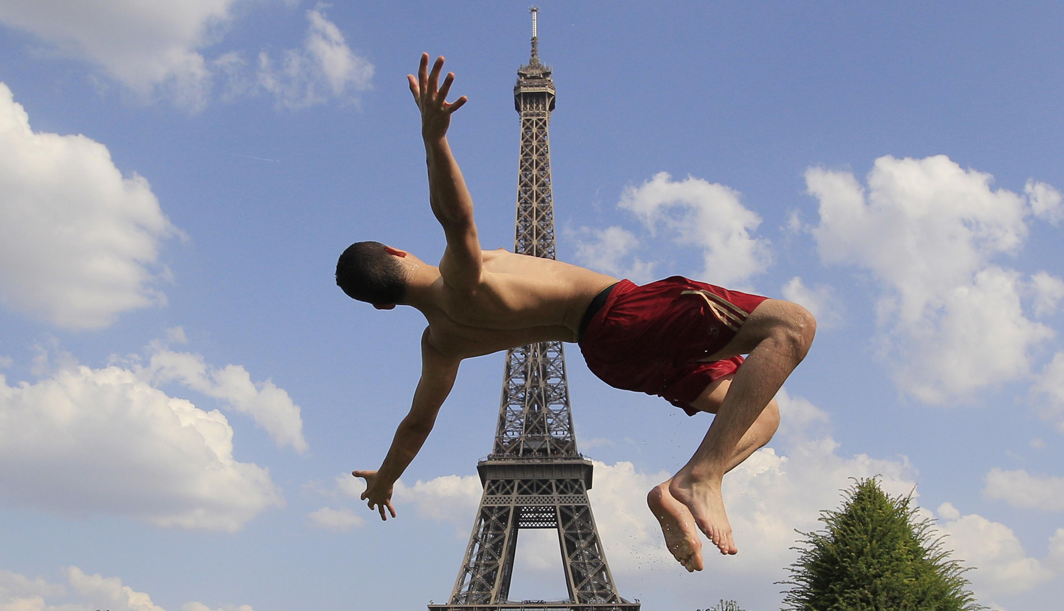 FRANÇA, 19.7.2013. Um rapaz salta numa fonte da praça Trocadero em frente da Torre Eiffel