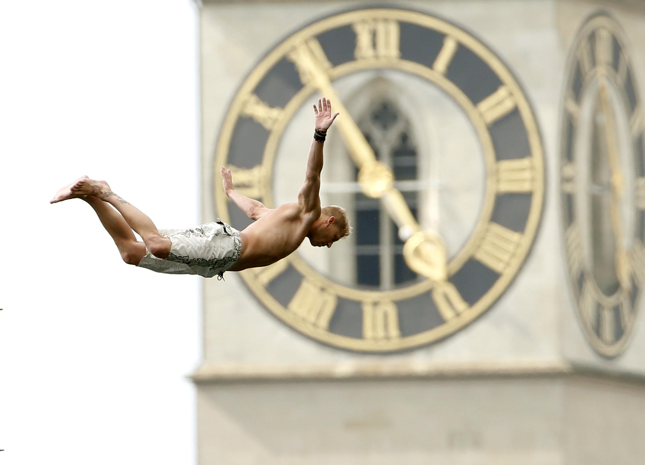 SUÍÇA, 25.7.2013. Um salto de uma plataforma de 10m para o lago Zurique, em Zurique, com a torre do relógio da igreja de S. Pedro ao fundo