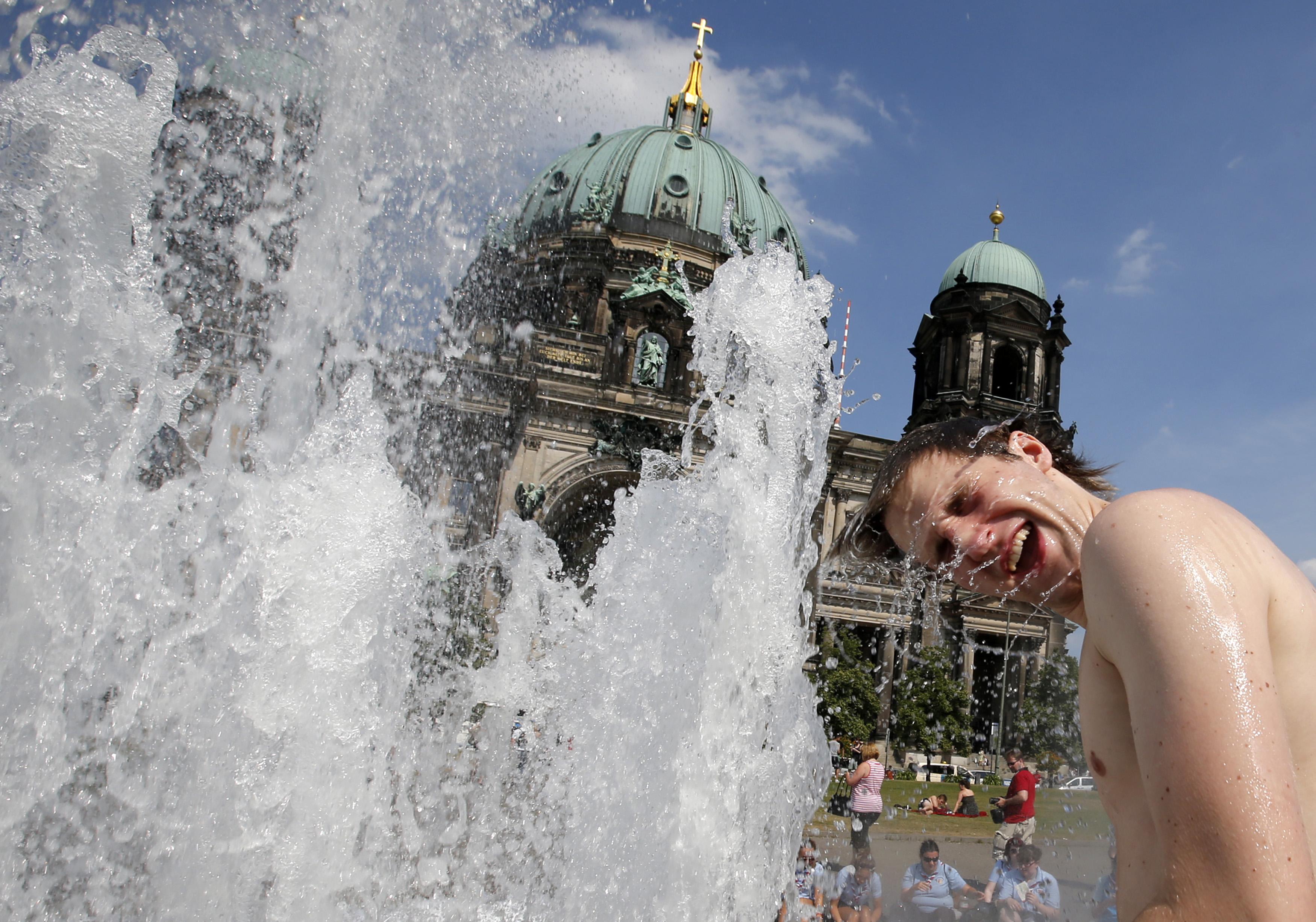 ALEMANHA, 27.7.2013. Frente à Catedral de Berlim, uma turista refresca-se em dia quente de Verão