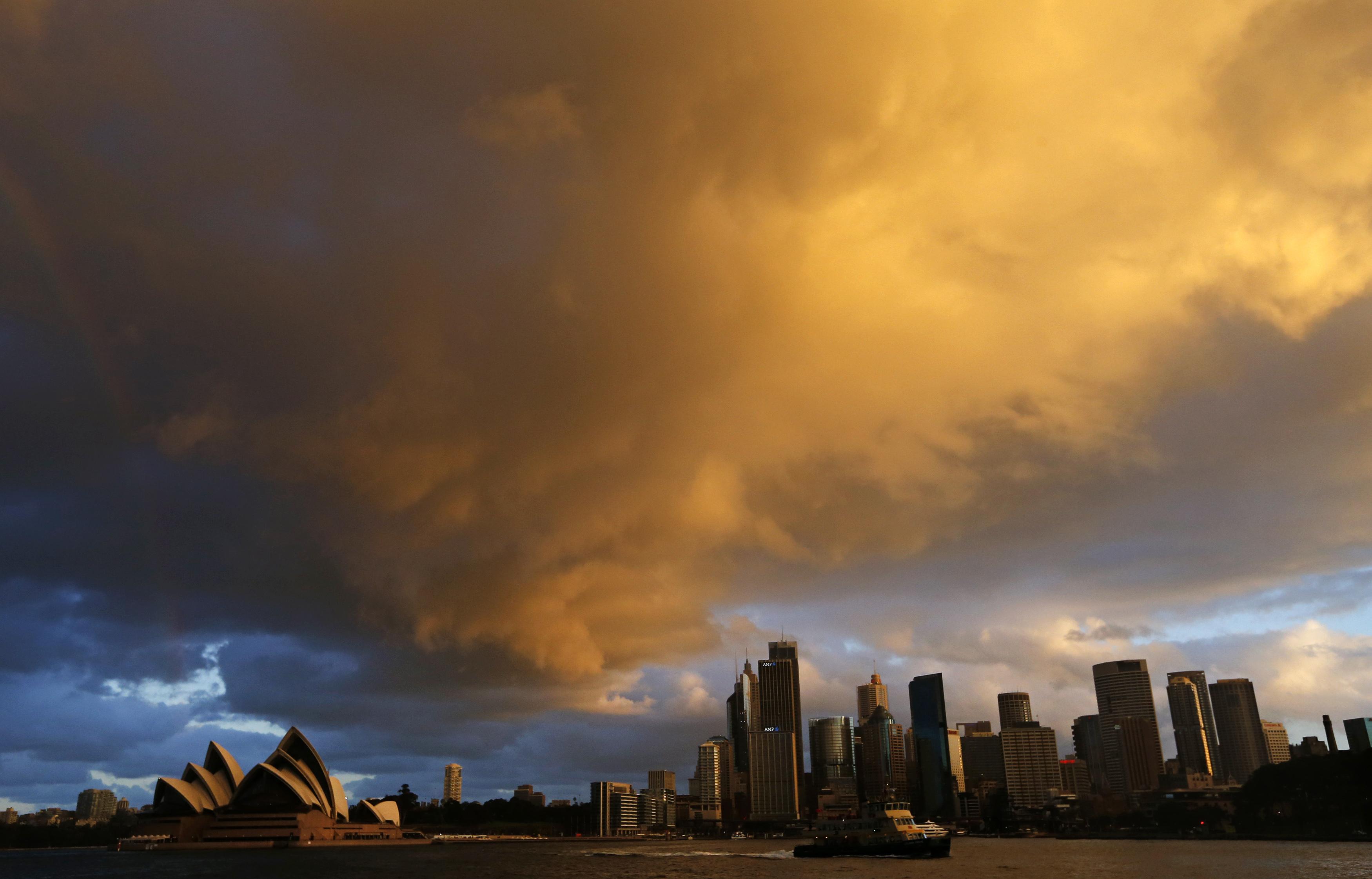 AUSTRÁLIA, 31.7.2013. Um ferry passa a Ópera de Sydney numa tarde muito quente