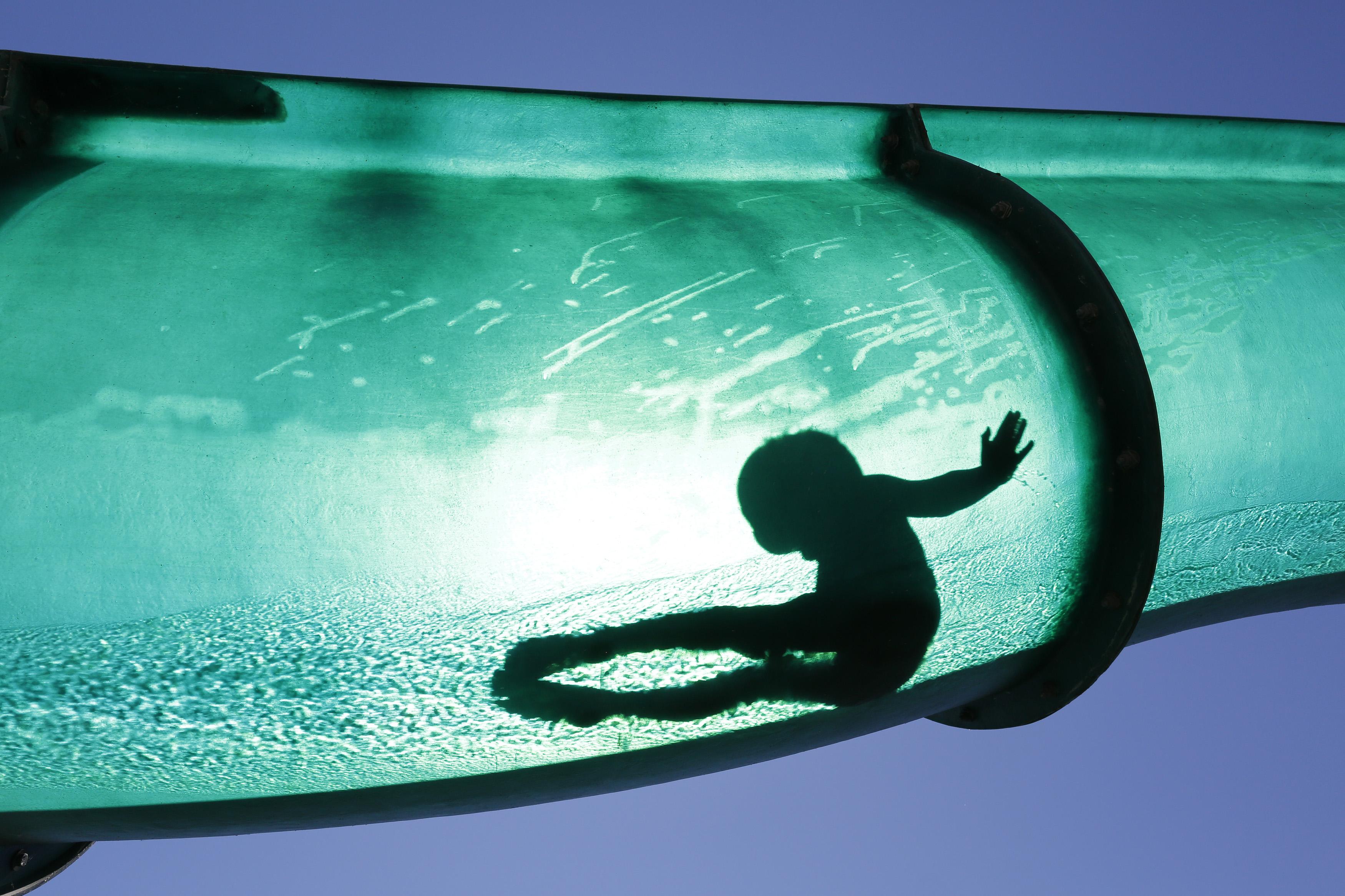SUÍÇA, 1.8.2013. Um rapaz num escorrega aquático num complexo de piscinas públicas em Thun
