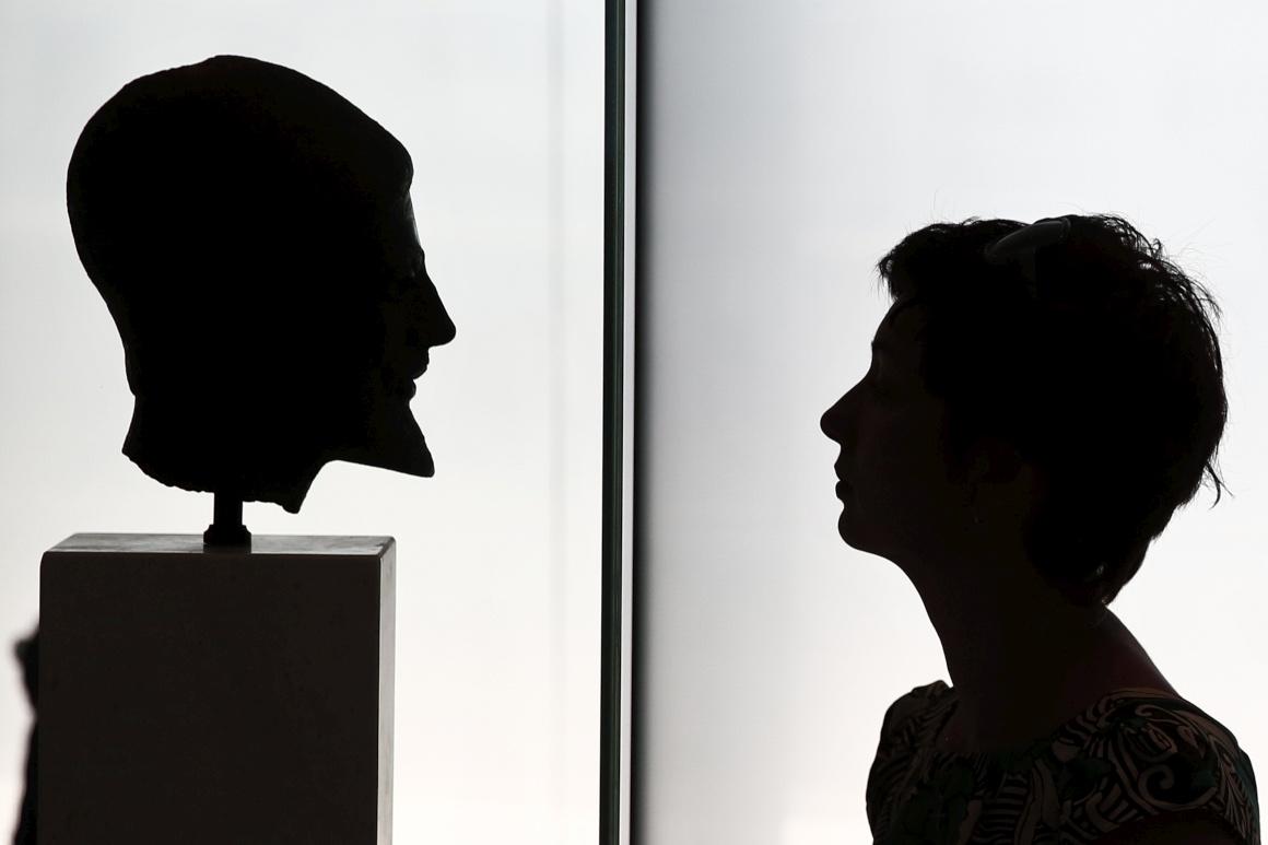 GRÉCIA, 13.08.2013. Uma visitante encara a cabeça em bronze de um hoplita (soldado da Grécia Antiga) no museu da Acrópole, em Atenas
