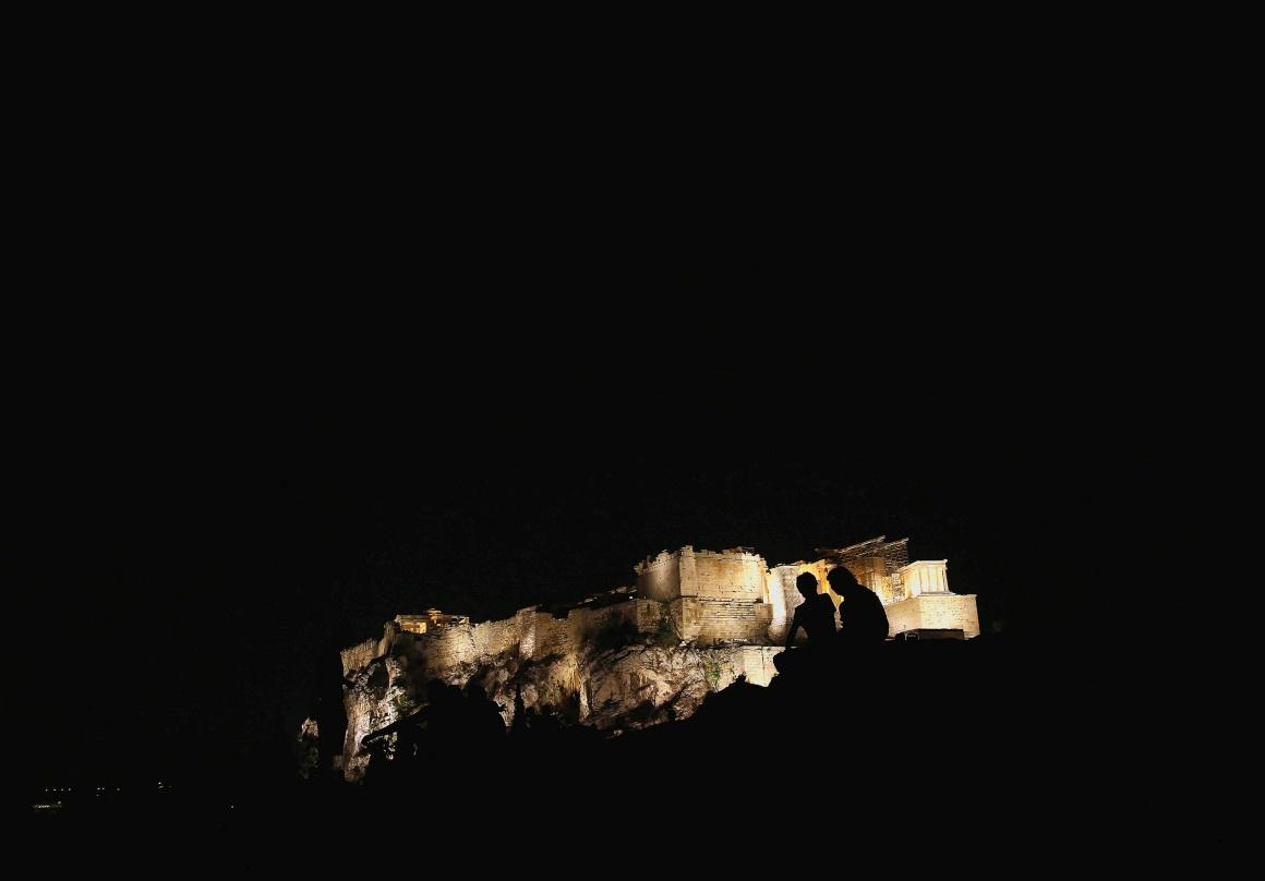 GRÉCIA, 14.08.2013. As silhuetas de um par de turistas contra detalhe da Acrópole em Atenas