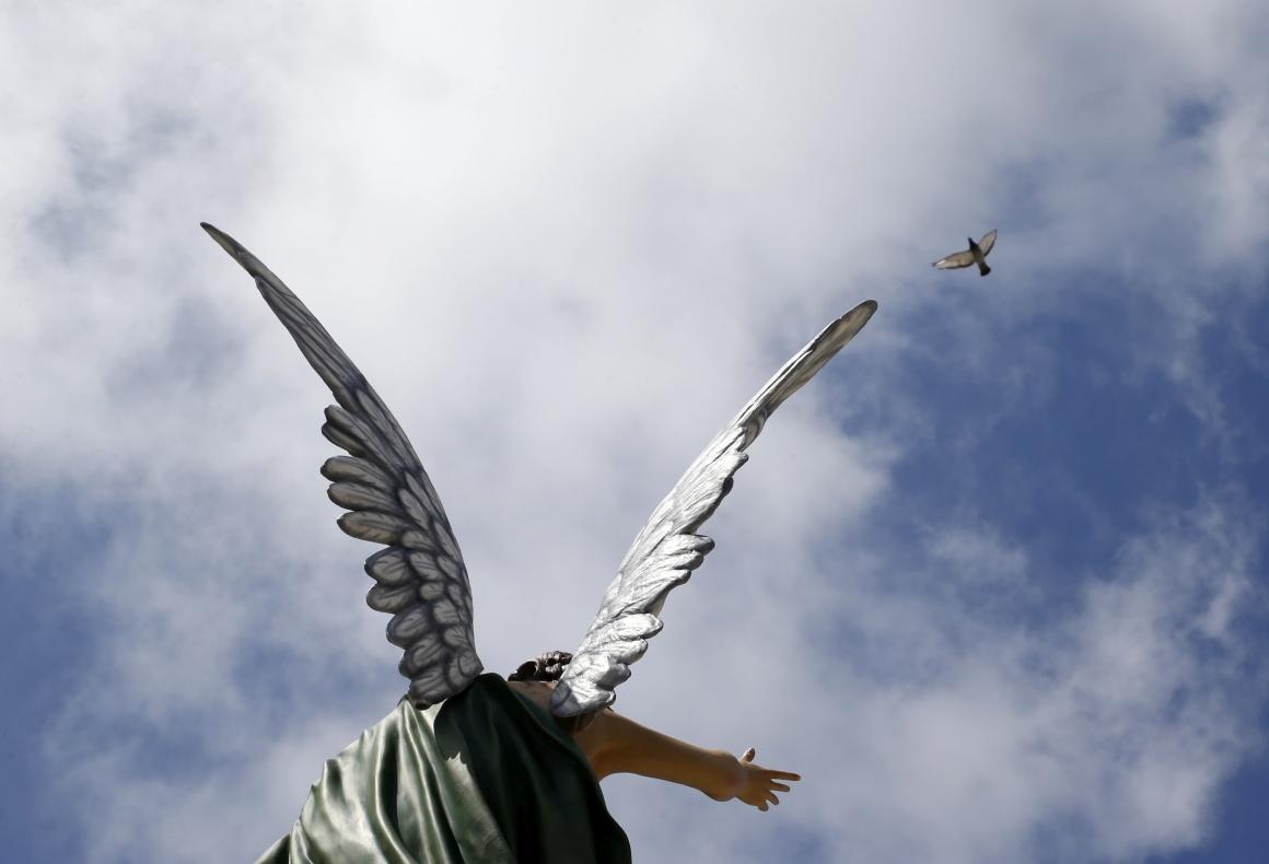 MALTA, 14.08.2013. Um pombo voa sobre a estátua de um anjo em Mgarr