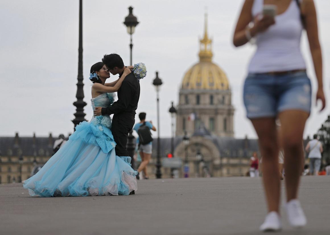 FRANÇA, 16.08.2013. Um casal na ponte Alexandre III com a Catedral de Saint Louis des Invalides no horizonte
