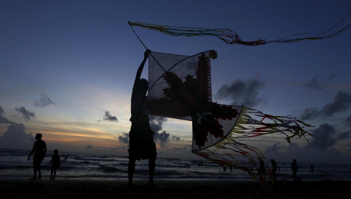 SRI LANKA, 18.08.2013. A silhueta de um rapaz com o seu papagaio de papel em Colombo