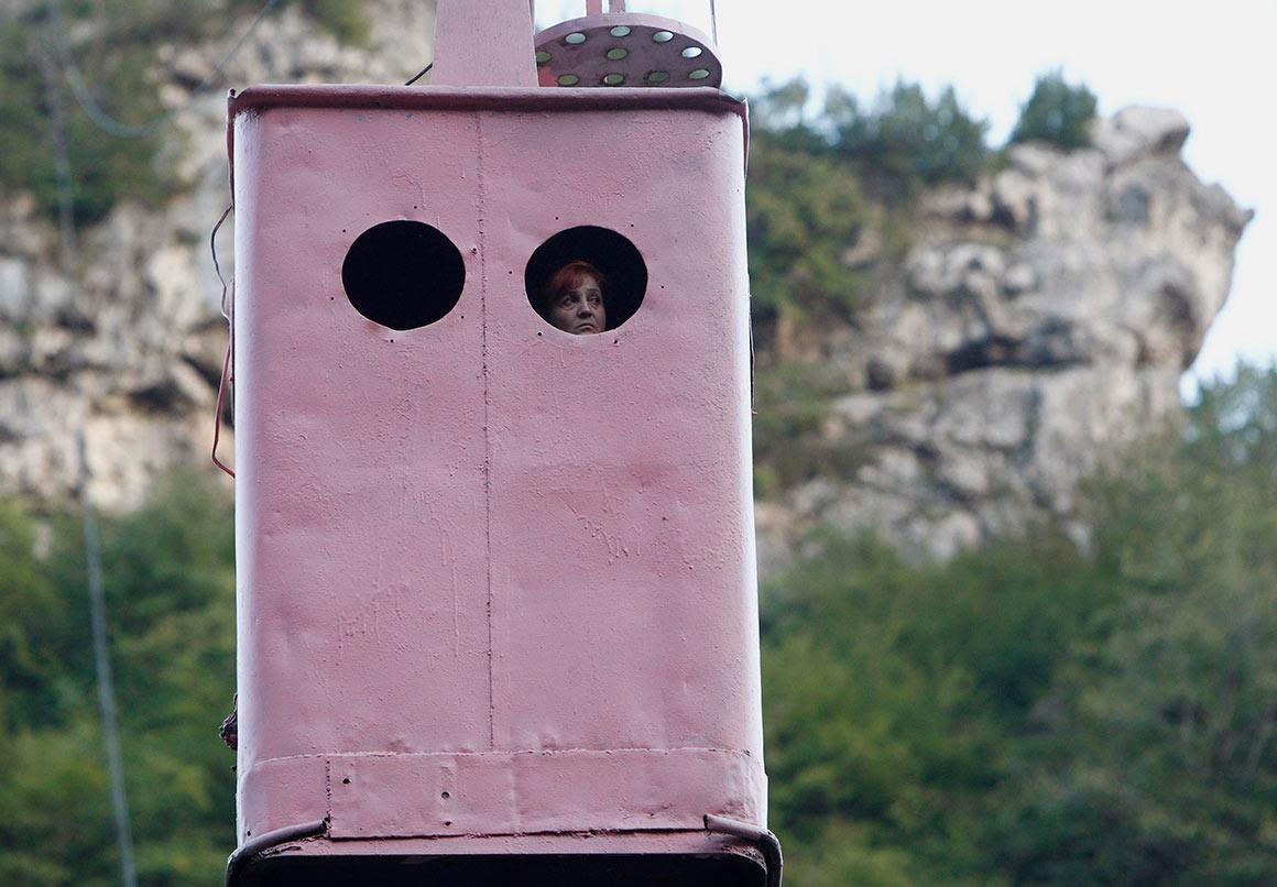 Passageira espreita pela janela de uma das cabines do teleférico de Chiatura