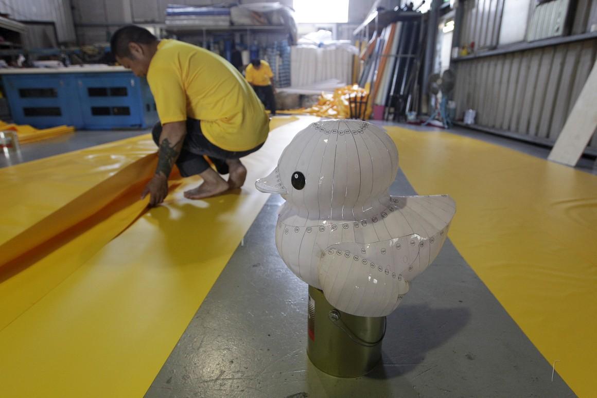 O modelo do pato que serve de base à sua construção. Um trabalhador chinês prepara o PVC para o pato