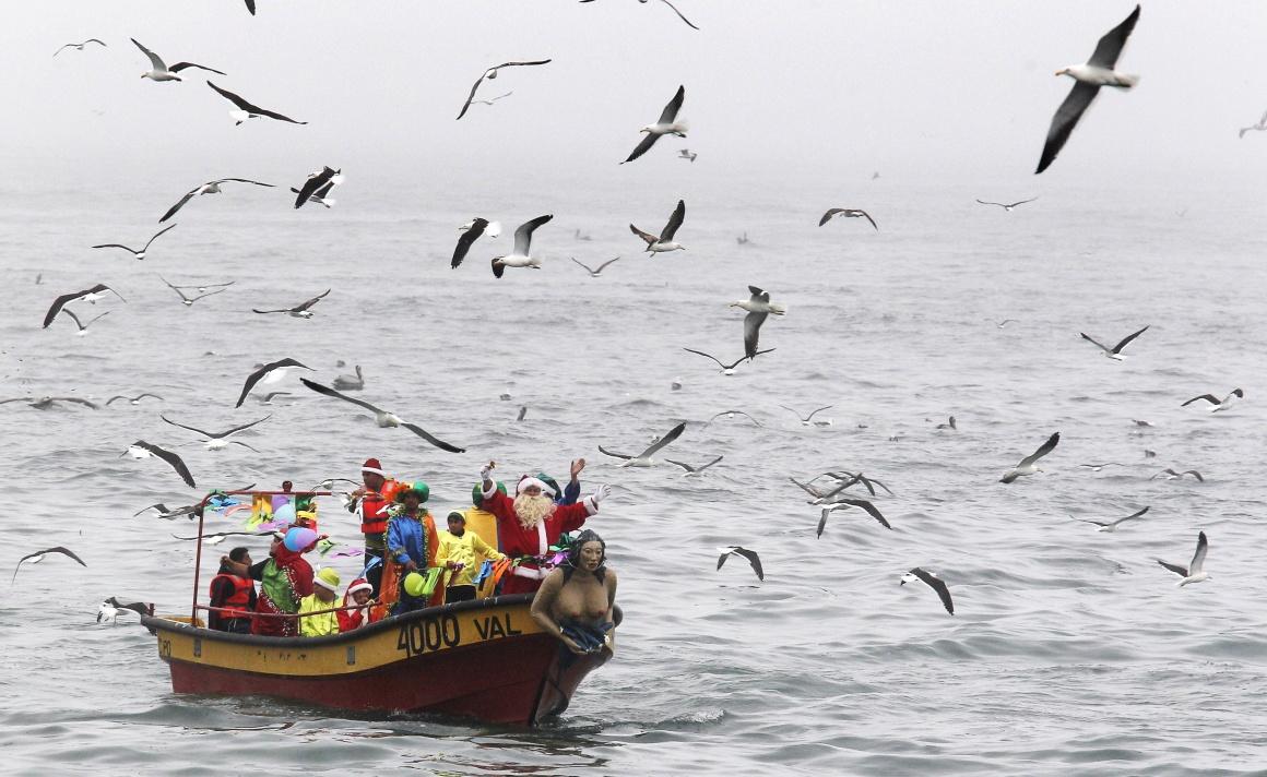 Chile, Valparaiso. Num barco de pescadores, na véspera de Natal, ao longo da costa de Valparaiso. Todos os anos, os pescadores organizam um barco natalício e ao longo da costa as pessoas esperam por estes Pais-Natal pescadores para receberem prendas e votos de felicidades