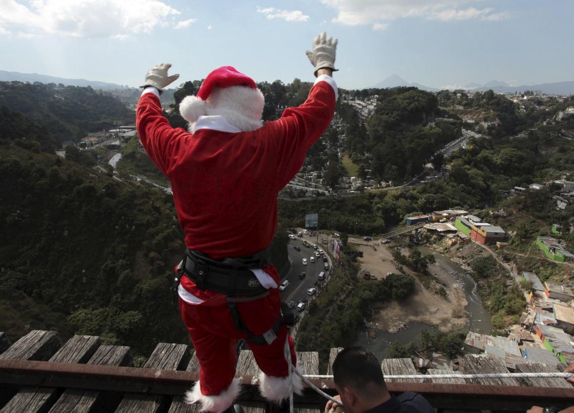 Guatemala. Um bombeiro vestido de Pai Natal prepara-se para descer em rappel a ponte para entregar presentes às crianças que vivem sob esta