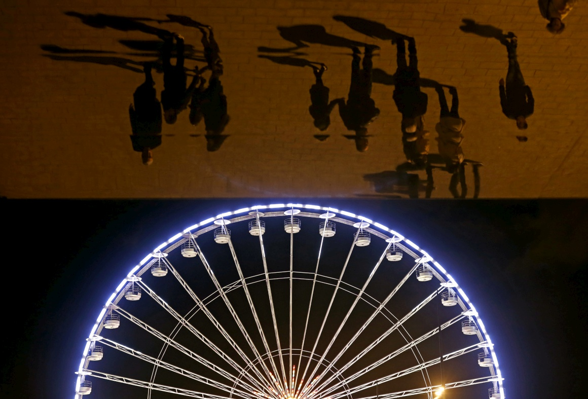 França, Marselha. Reflexos de visitantes em painéis espelhados desenhados por Norman Foster e um detalhe de uma roda gigante de feira de Natal